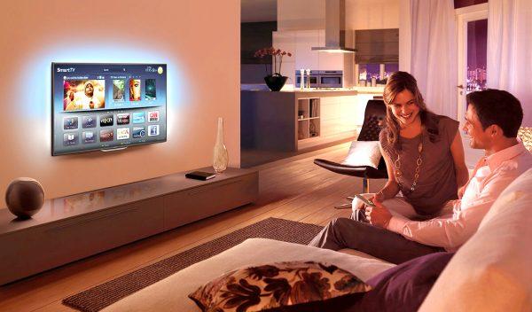 Молодая пара смотрит телевизор с функцией Smart TV