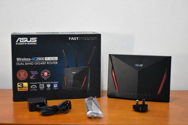 Wi-Fi-роутер Asus RT-AC86U стоит рядом с коробкой и переходниками на столе