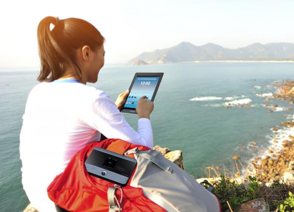 Девушка у моря с планшетом в руке и портативным роутером в рюкзаке